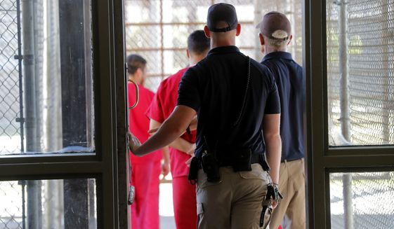 Under a proposed Justice Department rule change, migrants arrested by Customs and Border Protection or U.S. Immigration and Customs Enforcement would have DNA samples taken and sent to the FBI, which would then put the DNA information into its Combined DNA Index System, or CODIS, database. (Associated Press/File)