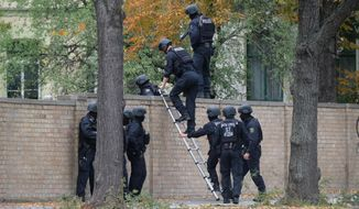 Police officers cross a wall at a crime scene in Halle, Germany, Wednesday, Oct. 9, 2019 after a shooting incident. A gunman fired several shots on Wednesday in the German city of Halle. Police say a person has been arrested after a shooting that left two people dead. (Sebastian Willnow/dpa via AP)