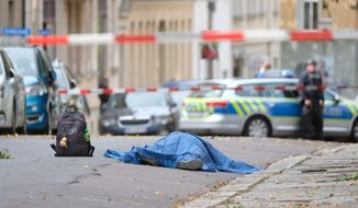 A body lies on a road in Halle, Germany, Wednesday, Oct. 9, 2019 after a shooting incident. A gunman fired several shots on Wednesday in German city of Halle and at least two got killed, according to local media FOCUS online. The gunman is on the run and police have sealed off the surrounding area. (Sebastian Willnow/dpa via AP)