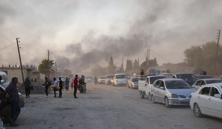 Syrians flee shelling by Turkish forces in Ras al Ayn, northeast Syria, Wednesday, Oct. 9, 2019. Turkish President Recep Tayyip Erdogan announced Wednesday the start of a Turkish military operation against Kurdish fighters in northeastern Syria. (AP Photo)