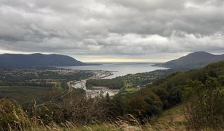 Warrenpoint village in the UK, Northern Ireland nestles on the banks of Carlingford Lough with its ferry that connects Northern Ireland, left of photo, with the Republic of Ireland, right, Wednesday, Sept. 25, 2019. The island of Ireland border issue has been the most intractable issue in the Brexit negotiations.  The ferry service that plys these calm waters is another sign that the border is all but invisible, but if the U.K. leaves the European Union on Oct. 31 without a Brexit divorce deal, this local boat could find itself plying an international border. (AP Photo/David Keyton)