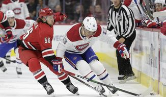 Carolina Hurricanes left wing Erik Haula (56), of Finland, reaches across Montreal Canadiens center Max Domi (13) during the first period of an NHL hockey game in Raleigh, N.C., Thursday, Oct. 3, 2019. (AP Photo/Gerry Broome)