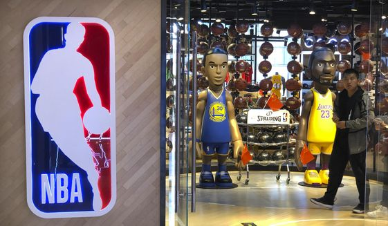 A man walks past statues of NBA players Stephen Curry of the Golden State Warriors, left, and Lebron James of the Los Angeles Lakers holding Chinese flags in the entrance of an NBA merchandise store in Beijing, Tuesday, Oct. 8, 2019. Chinese state broadcaster CCTV announced Tuesday it will no longer air two NBA preseason games set to be played in the country. (AP Photo/Mark Schiefelbein) **FILE**