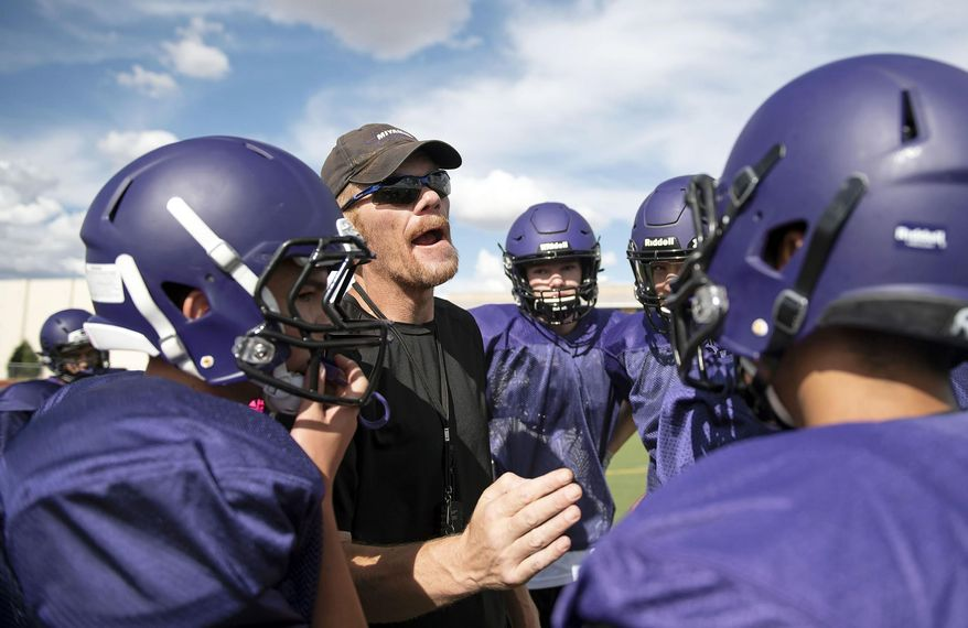 In this Aug. 7, 2019 photo, then-Miyamura High School Patriots football head coach John Roanhaus huddles with the team in their first week of practice to open the football season in Gallup, N.M. Roanhaus was arrested Saturday, Oct. 5, 2018, after authorities say a student used cell video to catch their coach taking money from a player's wallet. (Alma E. Hernandez/Gallup Independent via AP)