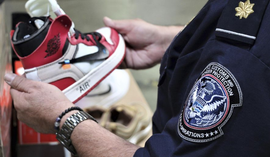 This undated photo provided by U.S. Customs and Border Protection shows an agent holding one of more than 14,800 pair of counterfeit Nike shoes, seized in a shipment arriving from China at the Los Angeles-Long Beach sports complex. The agency said Wednesday, Oct. 9, 2019 that had the fake special edition and retro design shoes been real, the manufacturer's suggested retail prices would have totaled more than $2.2 million. The agency says the shoes violated trademarks for various versions of Nike's Air Jordan and Air Max shoes. (U.S. Customs and Border Protection via AP)