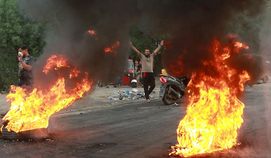 FILE - In this Sunday, Oct. 6, 2019 file photo, anti-government protesters set fires and close a street during a demonstration in Baghdad, Iraq. The protests have plunged the country into a new cycle of instability since last week, one that could potentially be the most dangerous this conflict-scarred nation has had to face, with more than 100 killed in less than a week. Iraqi security forces have been shooting at young Iraqis demanding jobs, electricity and clean water and an end to corruption. (AP Photo/Khalid Mohammed, File)