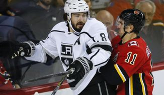 Los Angeles Kings' Drew Doughty, left, is checked by Calgary Flames' Mikael Backlund during the first period of an NHL hockey game Tuesday, Oct. 8, 2019, in Calgary, Alberta. (Jeff McIntosh/The Canadian Press via AP)
