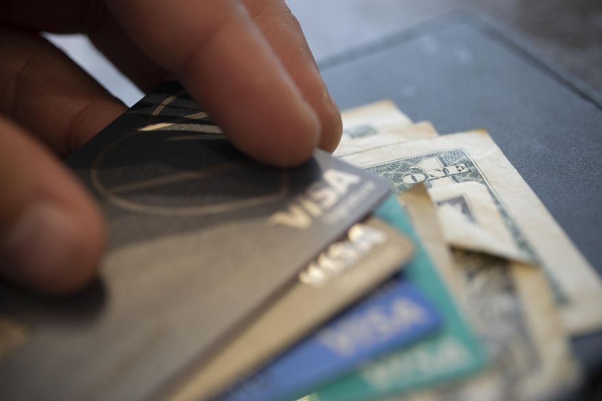 In this Aug. 11, 2019, photo a man puts his Visa card on a stack of cards for a split check at a restaurant in New Orleans. According to a NerdWallet study $35 is the average fee the country's largest banks charge customers who overdraw their accounts. (AP Photo/Jenny Kane)