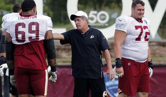 In this Aug. 5, 2019, file photo, Washington Redskins offensive line coach Bill Callahan, center, talks with tackle Hugh Thornton (69) during NFL football training camp in Richmond, Va. Jay Gruden was fired as head coach of the Washington Redskins on Monday, Oct. 7, 2019, after an 0-5 start to the sixth season of a tenure that featured only one playoff appearance. A person familiar with the team's plans told The Associated Press that offensive line coach Bill Callahan would replace Gruden on an interim basis. (AP Photo/Steve Helber, File) **FILE**