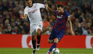Barcelona's Lionel Messi, right, vies for the ball with Sevilla's Daniel Carrico during Spanish La Liga soccer match between Barcelona and Sevilla at the Camp Nou stadium in Barcelona, Sunday, Oct. 6, 2019. (AP Photo/Joan Monfort)