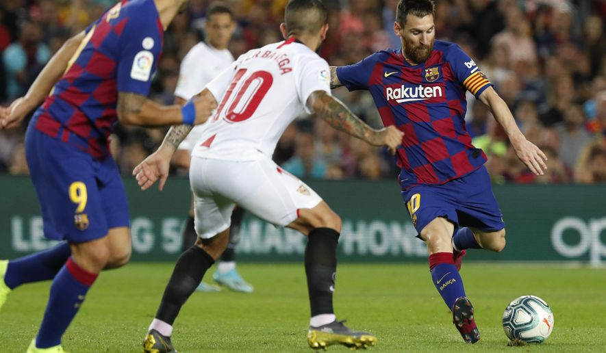 Barcelona's Lionel Messi, right, shoots the ball next to Sevilla's Ever Banega during Spanish La Liga soccer match between Barcelona and Sevilla at the Camp Nou stadium in Barcelona, Sunday, Oct. 6, 2019. Messi scored once in Barcelona's 4-0 victory. (AP Photo/Joan Monfort)