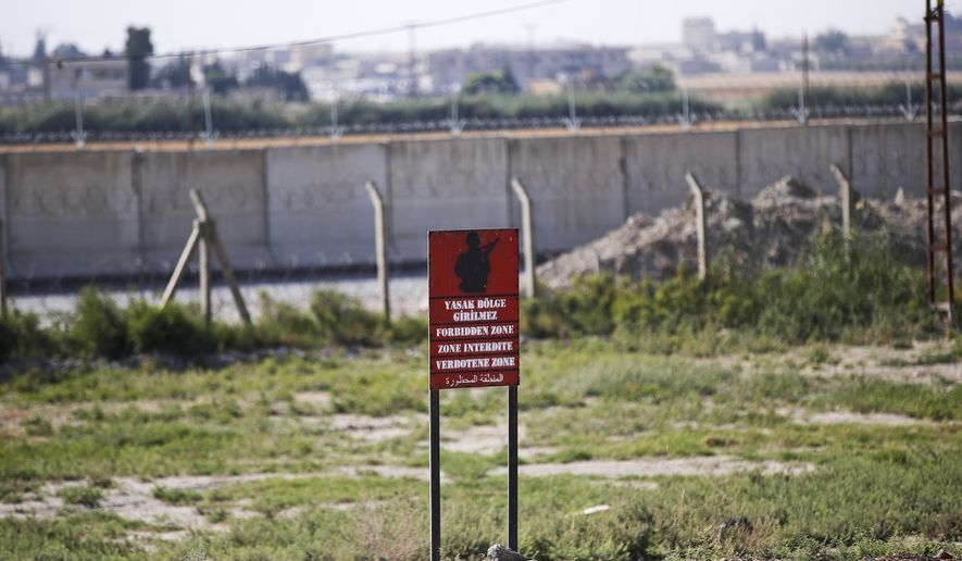 A view of the border between Turkey and Syria, in Akcakale, Sanliurfa province, southeastern Turkey, Tuesday, Oct. 8, 2019. The Turkey - Syria border has became a hot spot as Turkish Vice President Fuat Oktay said Turkey was intent on combatting the threat of Syrian Kurdish fighters across its border in Syria. (AP Photo/Lefteris Pitarakis)