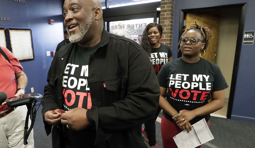 Former felon Desmond Meade and president of the Florida Rights Restoration Coalition, left, arrives with family members at the Supervisor of Elections office Tuesday, Jan. 8, 2019, in Orlando, Fla., to register to vote. Former felons in Florida began registering for elections on Tuesday, when an amendment that restores their voting rights went into effect. (AP Photo/John Raoux)