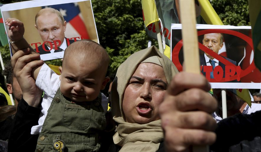 A Kurdish woman living in Cyprus holds up a baby as she shouts slogans in front of the U.S. embassy to protest Turkey's offensive into Syria, in Nicosia, Cyprus, Thursday, Oct. 10, 2019. The protesters, waving Cypriot and Kurdish flags as well as placards pledging support for Syria's Kurdish population, chanted slogans condemning Turkey's military action and urged for the withdrawal of Turkish forces. (AP Photo/Petros Karadjias)