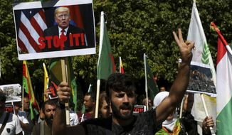 A Kurd living in Cyprus shouts slogans and holds a banner showing the U.S President Donald Trump, in front of the U.S. embassy to protest Turkey's offensive into Syria, in Nicosia, Cyprus, Thursday, Oct. 10, 2019. The protesters, waving Cypriot and Kurdish flags as well as placards pledging support for Syria's Kurdish population, chanted slogans condemning Turkey's military action and urged for the withdrawal of Turkish forces. (AP Photo/Petros Karadjias)