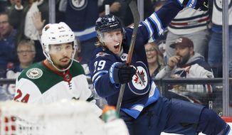 Winnipeg Jets' Patrik Laine (29) celebrates his goal as Minnesota Wild's Matt Dumba (24) skates by during the second period of an NHL hockey game Thursday, Oct. 10, 2019, in Winnipeg, Manitoba. (John Woods/The Canadian Press via AP)