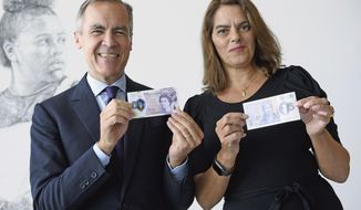 Governor of the Bank of England Mark Carney and artist Tracey Emin pose together to unveil the new 20 pound bank note, featuring a portrait of the English artist JMW Turner, at the Turner Gallery in London, Thursday Oct. 10, 2019.  The new polymer twenty pound note which contains sophisticated security features, will be issued into general circulation early 2020. (Leon Neal/PA via AP)