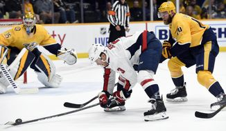 Washington Capitals defenseman Nick Jensen (3) reaches for the puck as Nashville Predators defenseman Mattias Ekholm (14), of Sweden, moves in during the first period of an NHL hockey game Thursday, Oct. 10, 2019, in Nashville, Tenn. (AP Photo/Mark Zaleski)