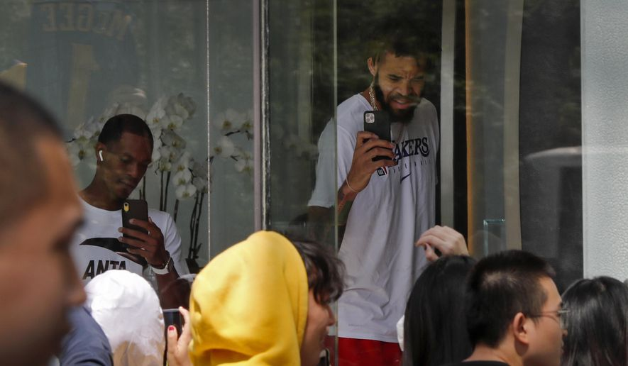 NBA players use their smartphones to film fans gathers outside the Ritz-Carlton hotel in Shanghai, China, Thursday, Oct. 10, 2019. NBA Commissioner Adam Silver told the Brooklyn Nets and Los Angeles Lakers on Wednesday that the league is still expecting them to play as scheduled this week, even while the rift between the league and Chinese officials continued in ways that clearly suggested the two planned games in Shanghai and Shenzhen were anything but guaranteed. (AP Photo/Andy Wong)