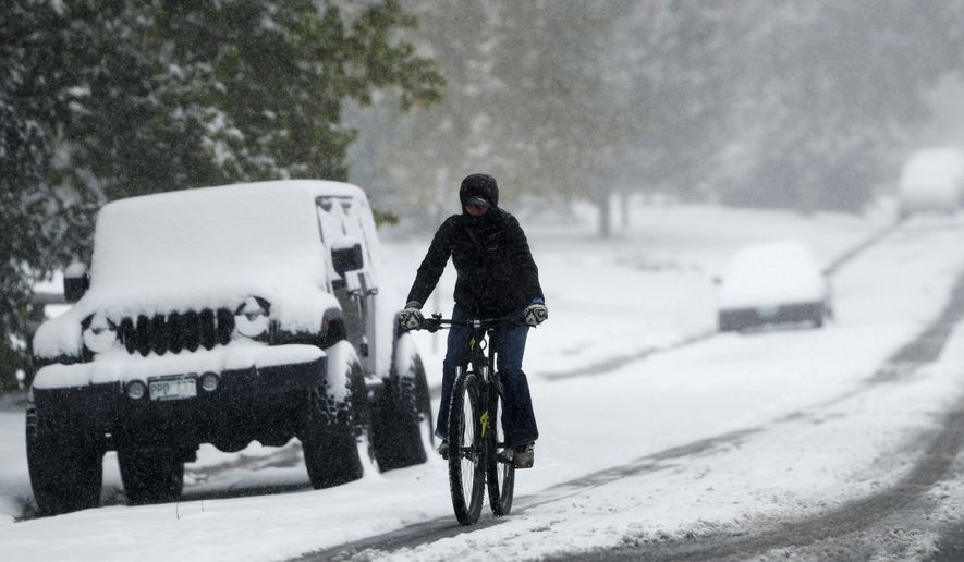 A bicyclist uses a tire track to guide her bicycle down South Monroe Street as the season's first snow storm sweeps over the metropolitan area Thursday, Oct. 10, 2019, in Denver. Forecasters predict that the snow will move out and cold temperatures will envelope the area as the storm moves on to the plains. (AP Photo/David Zalubowski)