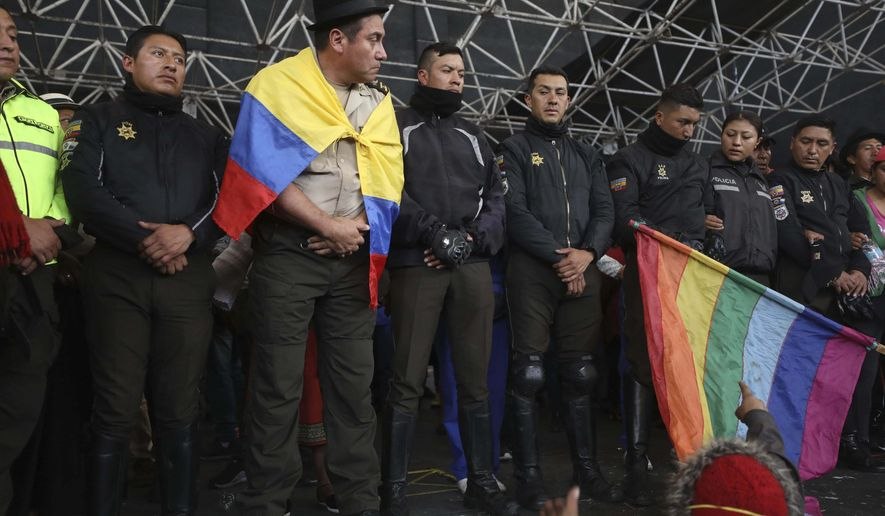 Police detained by anti-governments protesters are presented on a stage in Quito, Ecuador, Thursday, Oct. 10, 2019. Thousands of protesters staged anti-government rallies Wednesday, seeking to intensify pressure on Ecuador's president after a week of unrest sparked by fuel price hikes. (AP Photo/Fernando Vergara)