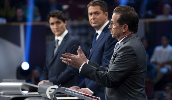 Liberal leader Justin Trudeau, left to right, Conservative leader Andrew Scheer and Bloc Quebecois leader Yves-Francois Blanchet take part in the Federal leaders French language debate in Gatineau, Quebec, Thursday, Oct. 10, 2019. (Chris Wattie/The Canadian Press via AP)