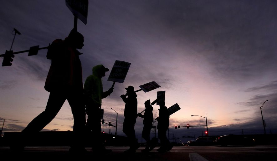 General Motors employees picket outside the Fairfax Assembly Plant in Kansas City, Kan. during the nationwide UAW strike against GM, Wednesday, Oct. 9, 2019. (AP Photo/Charlie Riedel)
