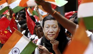 An Indian schoolgirl wears a face mask of Chinese President Xi Jinping to welcome him on the eve of his visit in Chennai, India, Thursday, Oct. 10, 2019. Chinese President Xi Jinping is coming to India to meet with Prime Minister Narendra Modi on Friday, just weeks after China supported Pakistan in raising the issue of India's recent actions in disputed Kashmir at the U.N. General Assembly meeting in New York. (AP Photo/R. Parthibhan)