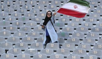 An Iranian woman waves her country's flag as she arrives at the Azadi Stadium to watch the 2022 World Cup qualifier soccer match between Iran and Cambodia, in Tehran, Iran, Thursday, Oct. 10, 2019. Iranian women are freely allowed into the stadium for the first time in decades. They had been banned since 1981. (AP Photo/Vahid Salemi)
