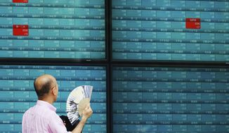 In this Thursday, Oct. 3, 2019, photo, a man looks at an electronic stock board showing Japan's Nikkei 225 index at a securities firm in Tokyo. Asian shares were mixed Thursday, Oct. 10, following broad gains on Wall Street as investors pondered mixed reports on the likelihood of progress in resolving the trade war between the U.S. and China. (AP Photo/Eugene Hoshiko)