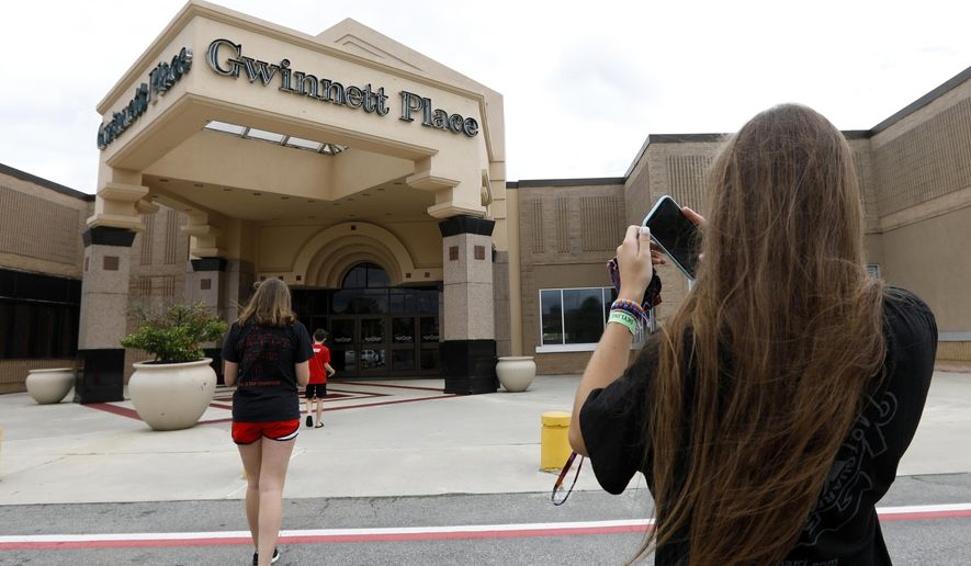 "In this July 23, 2019 file photo, Brinley Rawson, a 17-year-old Stranger Things fan from Gwinnett County, snaps a photo of Gwinnett Place Mall in Duluth, Ga.  The Georgia mall heavily featured in the latest season of Netflix's ""Stranger Things"" is going up for sale.  Moonbeam Capital Partners is ready to sell its portion of the long-struggling Gwinnett Place Mall, which has been so empty that a body went unnoticed near the food court for about two weeks in 2017. (AP Photo/Andrea Smith, File) **FILE**"
