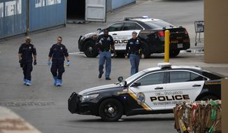 FILE - In this Tuesday, Aug. 6, 2019 file photo, police officers walk behind a Walmart at the scene of a mass shooting at a shopping complex, in El Paso, Texas. Suspect Patrick Crusius who was indicted for the killing of 22 people in the mass shooting at a Texas Walmart is set to formally hear the charges against him in an El Paso courtroom. An arraignment hearing for Crusius is set for Thursday, Oct. 10. (AP Photo/John Locher, File)