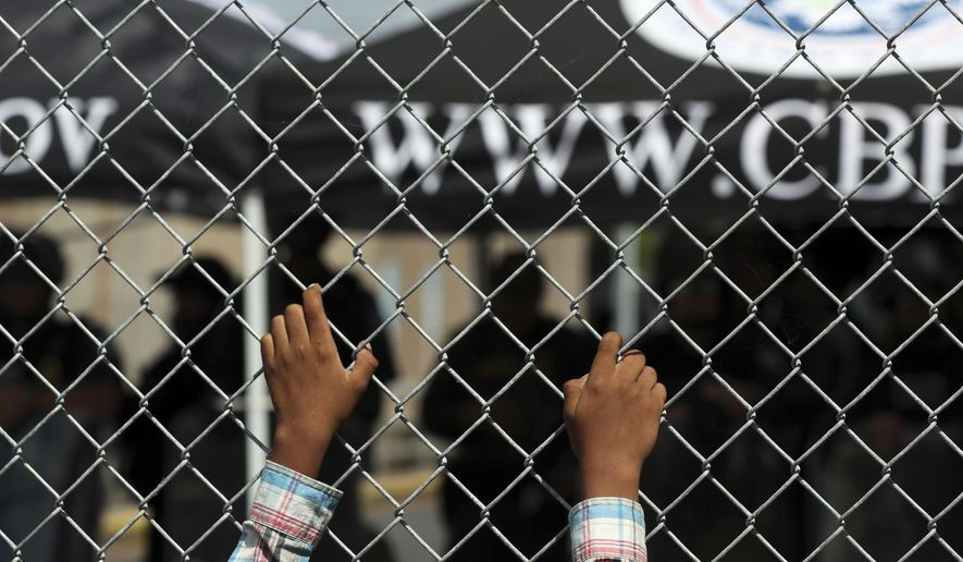 A migrant leans on a fence of the Gateway International Bridge that connects downtown Matamoros, Mexico with Brownsville, Thursday, Oct. 10, 2019. Migrants wanting to request asylum camped out on the international bridge leading from Mexico into Brownsville, Texas, causing a closure of the span. (AP Photo/Fernando Llano)