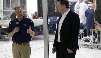 NASA Administrator Jim Bridenstine, left, talks with SpaceX chief engineer Elon Musk, right, in front of the Crew Dragon spacecraft, about the progress to fly astronauts to and from the International Space Station, from American soil, as part of the agency's commercial crew program at SpaceX headquarters, in Hawthorne, Calif., Thursday, Oct. 10, 2019. (AP Photo/Alex Gallardo)