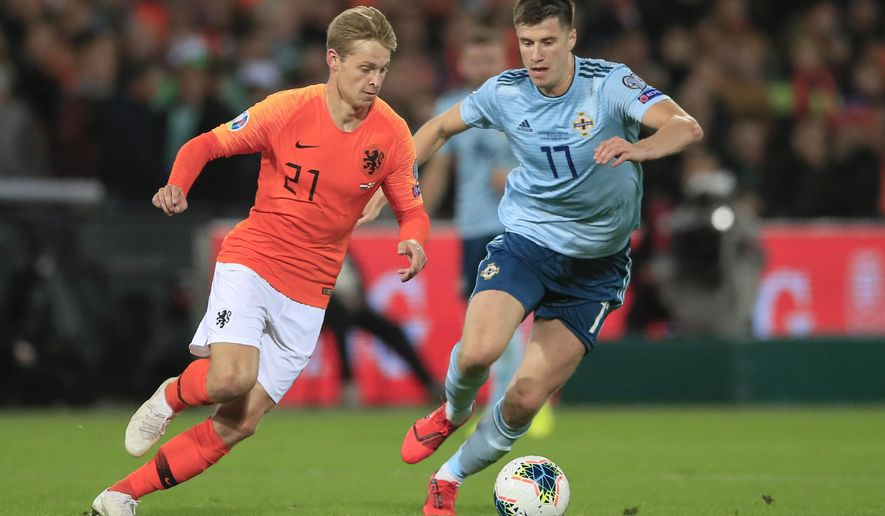 Netherlands' Frenkie de Jong, left, challenges for the ball with Northern Ireland's Paddy McNair during the Euro 2020 group C qualifying soccer match between The Netherlands and Northern Ireland at De Kuip stadium in Rotterdam, Netherlands, Thursday, Oct. 10, 2019. (AP Photo/Peter Dejong)