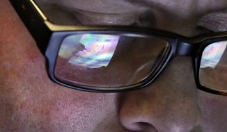 FILE- In this April 11, 2019, file photo trader Jeffrey Vazquez's glasses reflect the screen of his handheld device as he works on the floor of the New York Stock Exchange. Investment brokerages suffered heavy damage to their stock values after Charles Schwab eliminated more of its fees and pushed others to follow. (AP Photo/Richard Drew, File)