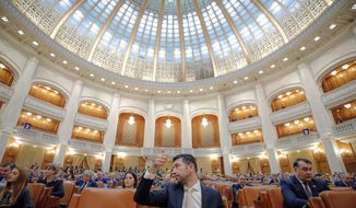 A Romanian member of parliament gives a thumbs up during procedures ahead of a no confidence vote in Bucharest, Romania, Thursday, Oct. 10, 2019. Romania's government is facing a no confidence vote called by opposition parties. (AP Photo/Vadim Ghirda)
