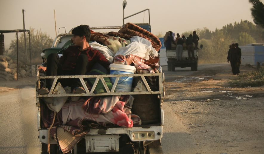 Syrians flee shelling by Turkish forces in Ras al Ayn, northeast Syria, Wednesday, Oct. 9, 2019. Turkish President Recep Tayyip Erdogan announced Wednesday the start of a Turkish military operation against Kurdish fighters in northeastern Syria. (AP Photo/Baderkhan Ahmad)