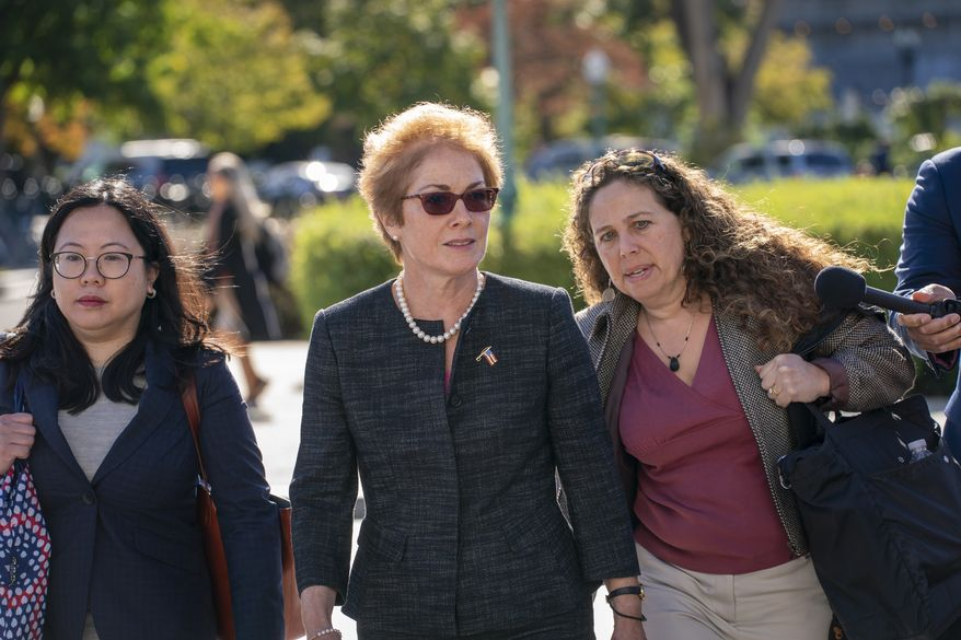 Former U.S. ambassador to Ukraine Marie Yovanovitch, center, arrives on Capitol Hill, Friday, Oct. 11, 2019, in Washington, as she is scheduled to testify before congressional lawmakers on Friday as part of the House impeachment inquiry into President Donald Trump. (AP Photo/J. Scott Applewhite)