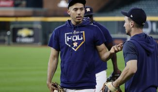 Houston Astros shortstop Carlos Correa, left, talks with teammate Alex Bregman, right, during a workout for a baseball American League Championship Series in Houston, Friday, Oct. 11, 2019. Houston will face the New York Yankees, Saturday. (AP Photo/Eric Gay)