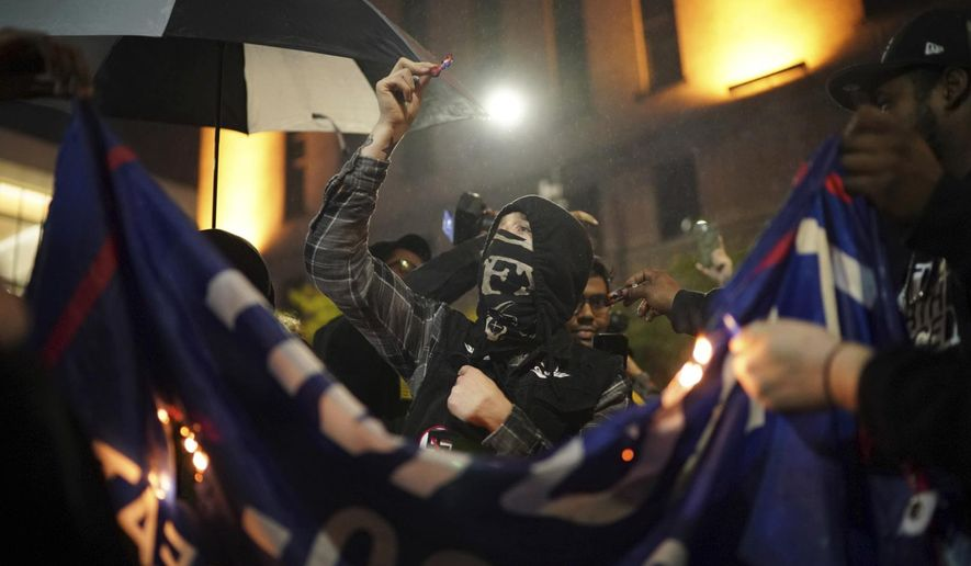 Protesters burn a flag outside President Donald Trump's campaign rally at the Target Center, Thursday, Oct. 10, 2019, in Minneapolis. Protesters got into a brief confrontation with police outside Trump's campaign rally after some of the demonstrators set Trump hats on fire. (Jeff Wheeler/Star Tribune via AP)