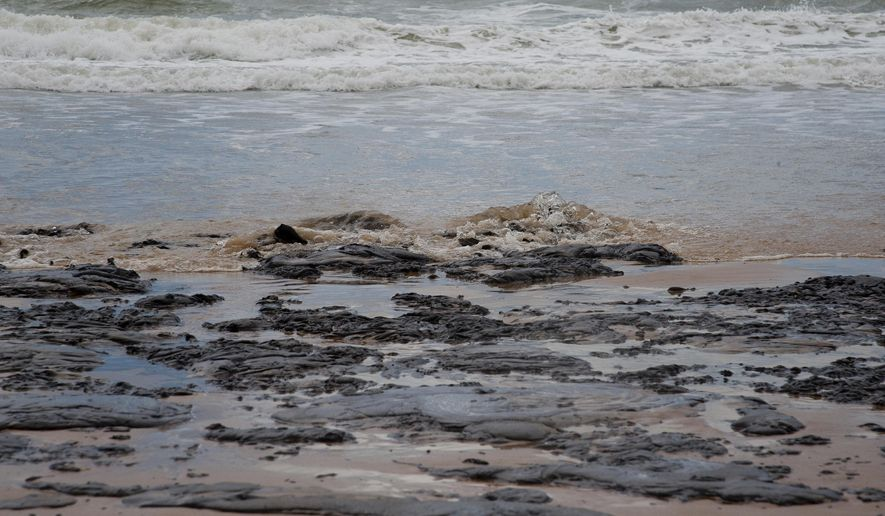 In this Sept. 25, 2019 photo released by the Sergipe state Government, an oil spill covers a beach on Sergipe state, Brazil. The spill started landing on Brazil's northeastern coast at the beginning of Sept., authorities say, and have now reached 61 municipalities in nine states, contaminating over 130 beaches. (Sergipe State Government via AP)