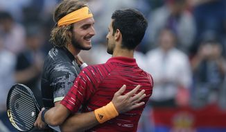 Stefanos Tsitsipas, left, of Greece is congratulated by Novak Djokovic of Serbia after winning in their men's singles quarterfinals match at the Shanghai Masters tennis tournament at Qizhong Forest Sports City Tennis Center in Shanghai, China, Friday, Oct. 11, 2019. (AP Photo/Andy Wong)