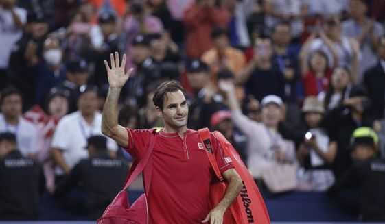 Roger Federer of Switzerland waves to spectators as he leaves the court after he lost to Alexander Zverev of Germany in their men's singles quarterfinals match at the Shanghai Masters tennis tournament at Qizhong Forest Sports City Tennis Center in Shanghai, China, Friday, Oct. 11, 2019. (AP Photo/Andy Wong)