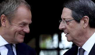 Cyprus' President Nicos Anastasiades, right, talks with European Council President Donald Tusk as he arrives for a meeting at the presidential palace in divided capital Nicosia, Cyprus, Friday, Oct. 11, 2019. Tusk is in Cyprus for one-day visit. (AP Photo/Petros Karadjias)