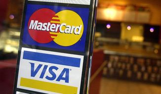 This April 22, 2005, file photo, shows logos for MasterCard and Visa credit cards at the entrance of a New York coffee shop. On Dec. 10, 2020, both Visa and Mastercard announced they will no longer process transactions for Pornhub. (AP Photo/Mark Lennihan, File)
