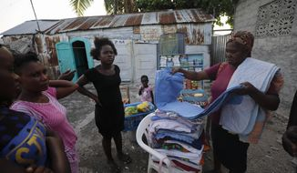 A vendor displays her wares for potential clients in front of a home partly built from the walls of portable toilets, in the Cite Soleil neighborhood of Port-au-Prince, Haiti, Thursday, Oct. 10, 2019. Residents of Cite Soleil say that their already limited access to basic services, work, and security has only been declining, and many are participating in the protests calling for the resignation of President Jovenel Moise. (AP Photo/Rebecca Blackwell)
