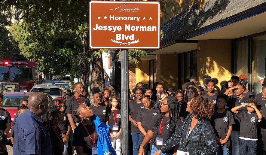 Students at the Jessye Norman School of the Arts unveil a sign naming the street outside the school in honor of the late opera star, Friday, Oct. 11, 2019, in Augusta, Ga. Norman, who won five Grammy awards including a lifetime achievement honor in her distinguished career, died on Sept. 30, at age 74. Her funeral is slated for Saturday and a benefit concert for the school follows on Sunday. (AP Photo/Jeffrey Collins)