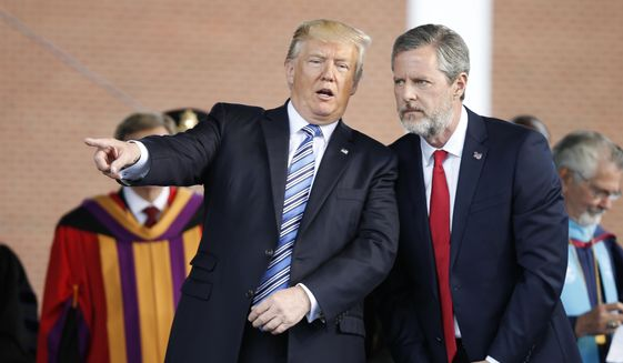 In this May 13, 2017, file photo, President Donald Trump gestures as he stands with Liberty University president, Jerry Falwell Jr., right, during commencement ceremonies at the school in Lynchburg, Va. (AP Photo/Steve Helber) ** FILE **