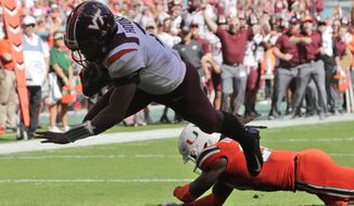 Virginia Tech quarterback Hendon Hooker (2) dives for a touchdown over Miami safety Robert Knowles (20) during the first half of an NCAA college football game, Saturday, Oct. 5, 2019, in Miami Gardens, Fla. (AP Photo/Lynne Sladky)